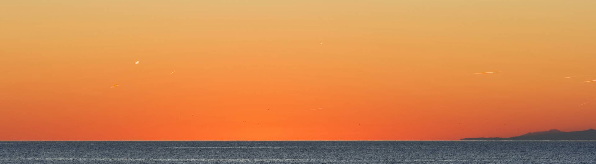 beautiful sunset in Mediterranean sea while a fishing boat returns to port